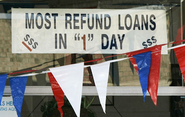 A sign promoting loans for instant tax refunds is displayed in a window in Little Rock, Arkansas, Tuesday, January 26, 2010.