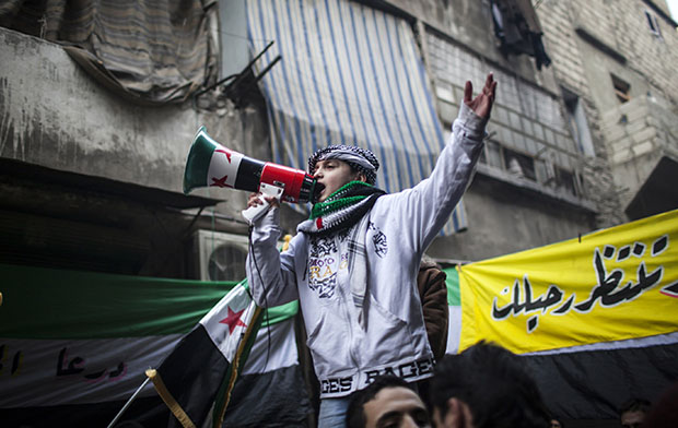 A child uses a megaphone to lead others in chanting Free Syrian Army slogans during a demonstration in the neighborhood of Bustan Al-Qasr, Aleppo, Syria, Friday, January, 4, 2013.