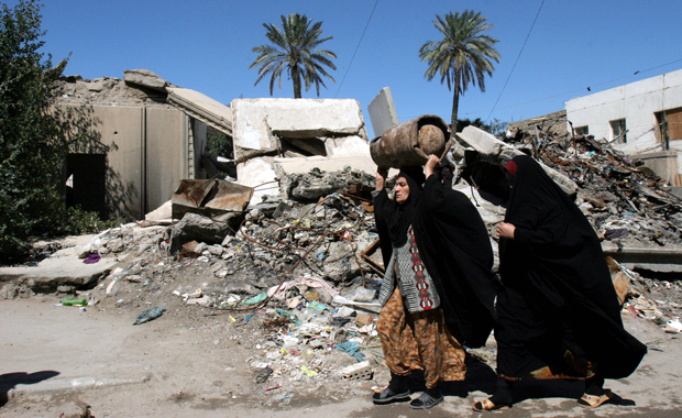 Iraqi women pass by a house destroyed during air campaign at early stages of war, in Baghdad, Iraq, March 18, 2007, ahead of the fourth anniversary of the U.S. invasion on Iraq. The 10th anniversary of the invasion is later this month.