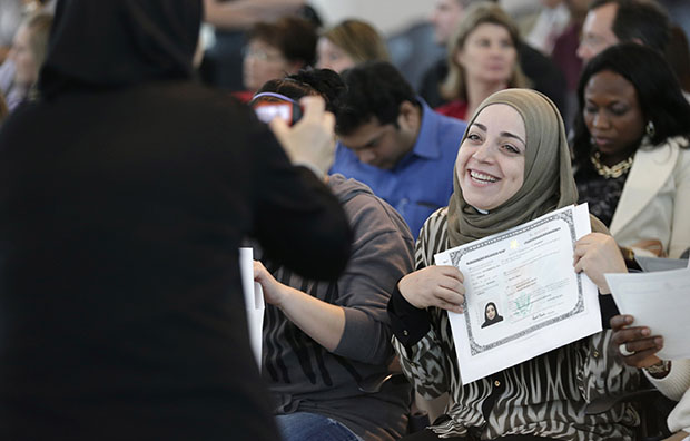 Miriam Bilaih shows off her U.S. citizen naturalization document after a naturalization ceremony Monday, January 28, 2013, in Irving, Texas.