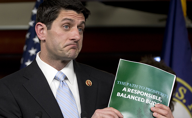 House Budget Committee Chairman Paul Ryan (R-WI) holds up a copy of the FY 2014 budget resolution as he speaks during a news conference on Capitol Hill in Washington, Tuesday, March 12, 2013.
