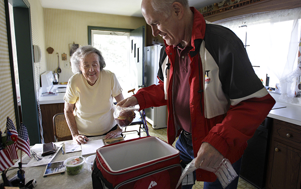 Marty Robertson unpacks food from the Chagrin Falls Meals on Wheels program for recipient Bernadette Winko, 90, in her Bentleyville, Ohio, home, Wednesday, March 14, 2012. The Ryan budget's additional $900 billion in nondefense discretionary spending cuts would further impede the ability of Meals on Wheels to combat senior hunger.