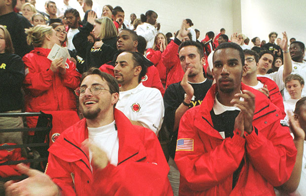 AmeriCorp volunteers Derek Haddad, left foreground, and Eddie Galan, right, both of Boston, applaud Friday, October 19, 2001, as they join some 1,000 new AmeriCorps members—who volunteer for one year to work in community service—during a rally to kick off their year of service.