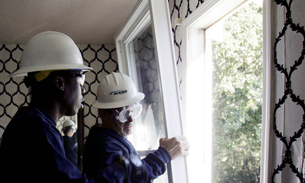 Richard Hucks, winterization project manager for South Carolina Electric & Gas Company, gets help from Demetrius Rumph, left, as they install energy-efficient windows in the home of Melba Jeffcoat in West Columbia, South Carolina.