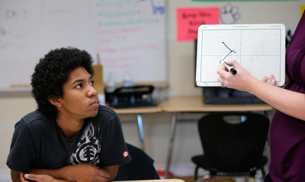 Noah Reyes, 11th grader, watches as teacher Crystal Kirch solves a problem in a pre-calculus class at Segerstrom High School in Santa Ana, California, Wednesday, January 16, 2013.