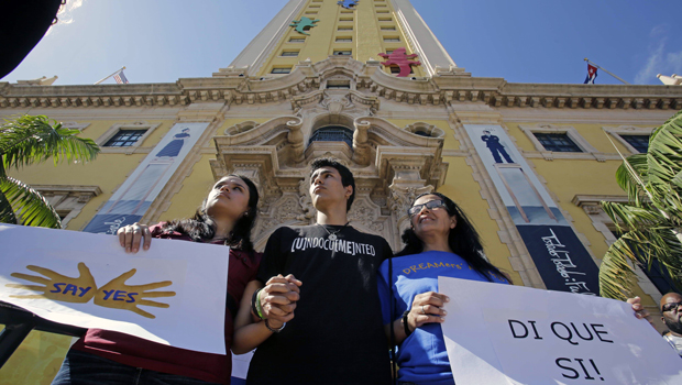 Federico Paseiro, center, his mother Patricia Sosa, right, both undocumented immigrants of Argentina, and his girlfriend Daysis Moraga, an immigration activist, left, hold signs in front of the Freedom Tower in downtown Miami, Monday, January 28, 2013.