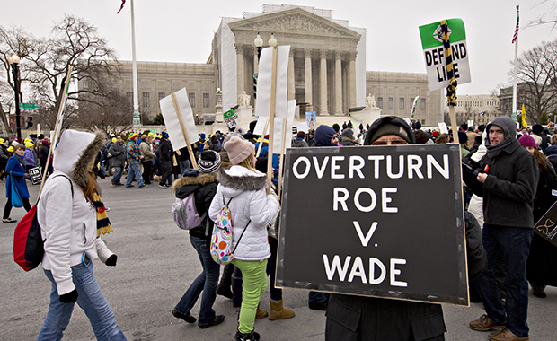 Antiabortion activists march past the U.S. Supreme Court in Washington, Friday, January 25, 2013, as they observe the 40th anniversary of the <em>Roe v. Wade</em> decision.