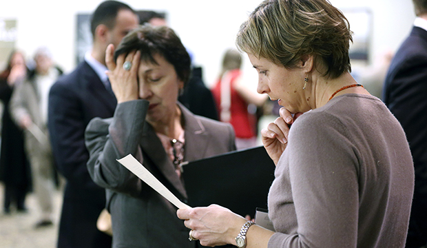 In this Monday, February 25, 2013, photo, Ann Oganesian, left, of Newton, Massachusetts, pauses as she speaks with a State Department employee about job opportunities with the federal government during a job fair in Boston.