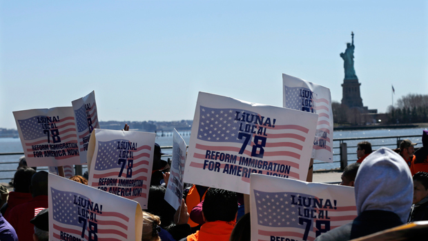 People look out at the Statue of Liberty while they hold signs Saturday, April 6, 2013, as members of New Jersey's congressional delegation as well as labor unions, religious leaders, immigrants, and immigration advocates rally at Liberty State Park in Jersey City, New Jersey.