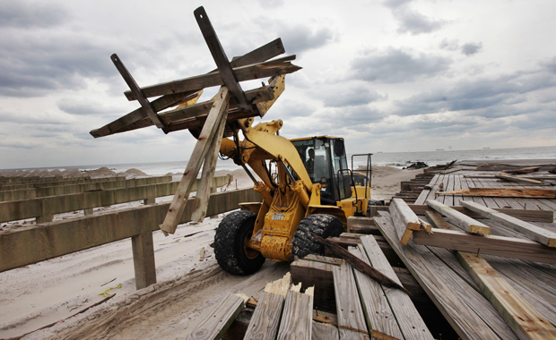 A front-end loader carries scraps of timber as it dismantles the storm-damaged boardwalk in Long Beach, New York, Friday, February 1, 2013. Three months after Superstorm Sandy devastated the coastal areas of New Jersey and New York, Congress finally passed a $50.5 billion bill to rebuild homes, businesses, utilities, mass transit, and other critical infrastructure.