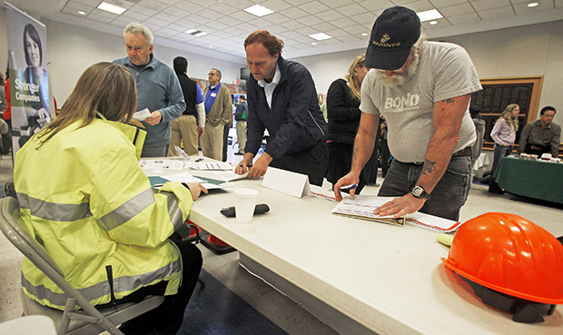 In this Thursday, April 3, 2013, photo, people fill out applications at the Green Mountain Flagging table at the 4th Annual Central Vermont Job Fair in Montpelier, Vermont.