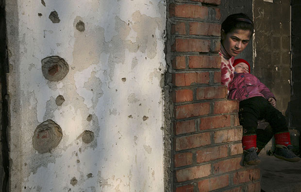 A Chechen girl holds her brother on the balcony of a flat in a destroyed house in Grozny, Chechnya, March 15, 2007.