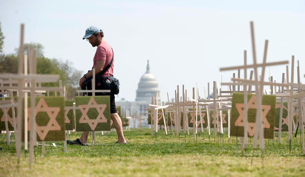 A man walks past thousands of grave markers erected in a mock cemetery to honor the victims of gun violence on the National Mall in Washington, Thursday, April 11, 2013.