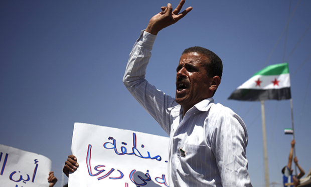 A Syrian refugee chants anti-Assad slogans and waves the victory sign during a strike at Zaatari refugee camp in Mafraq, Jordan, Thursday, April 25, 2013.