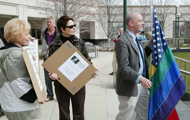 Joanne Polisano, left, Mary Czartoryski, center, and Stephen Eddins join others in a rally outside the Michigan Hall of Justice in Lansing, Michigan, on April 11, 2006, following a state court of appeals hearing on whether governments and public universities can provide health insurance and other benefits to the partners of gay employees without violating the state constitution.