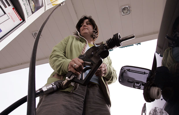 A customer pumps gas at a gas station in Menlo Park, California. Even though many middle-class programs are facing cuts, the big five oil companies continue to enjoy huge profits and tax breaks.