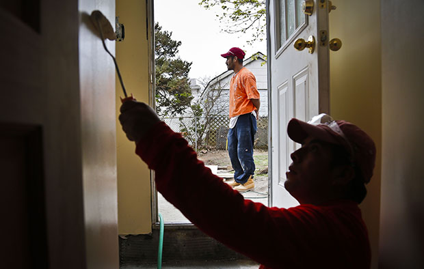 Victoriano Del La Cruz, 36, a carpenter from Mexico, stands just outside a basement entrance as Sergio Ajche, 29, from Guatemala, finishes a painting job in New York, May 7, 2013. Providing undocumented immigrants with a pathway to legalization and citizenship would have many benefits for the U.S. economy,