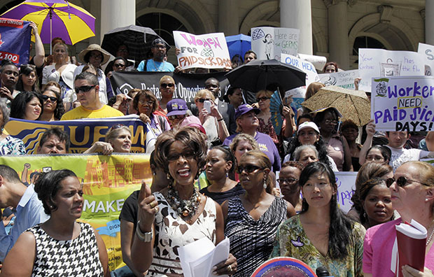 Marjorie Hill, second on the left, CEO of the Gay Men's Health Crisis, addresses the Women for Paid Sick Days rally on the steps of New York's City Hall, Wednesday, July 18, 2012.