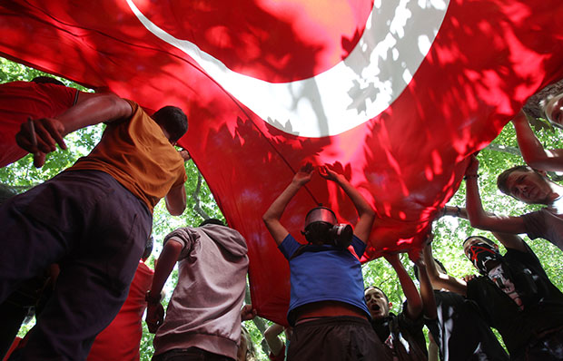 High school students hold up a Turkish flag during a protest at Gezi Park in Taksim Square in Istanbul, Turkey, Monday, June 3, 2013.
