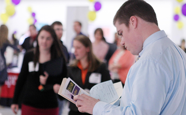 In this April 4, 2012, file photo, Scott Richards of Saint Anselm College looks over possible jobs during a career fair for college students in Manchester, New Hampshire.