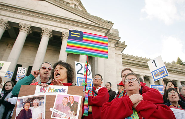 Linda Baker, foreground left, of Renton, Washington, and Kim Nuesse, right, of Kelso, Washington, join others on the Capitol steps during a rally in support of legislation to protect gay and lesbian citizens from discrimination in housing, employment, and insurance, January 23, 2006, in Olympia, Washington.