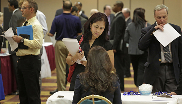In this May 29, 2013, photo, job seeker Anu Vatal of Chicago speaks with Patrice Tosi of BluePay, seated, during a career fair in Rolling Meadows, Illinois.