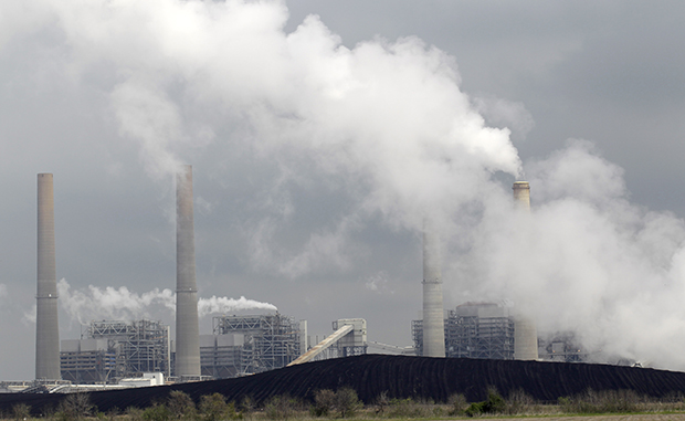 In this Wednesday, March 16, 2011, file photo, exhaust rises from smokestacks in front of piles of coal at NRG Energy's W.A. Parish Electric Generating Station in Thompsons, Texas.