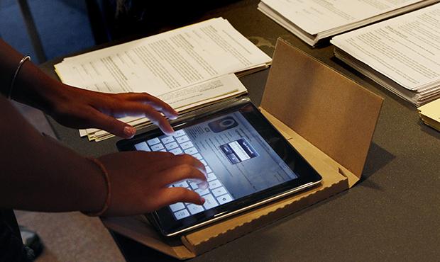 A student unpacks a new iPad at Burlington High School in Burlington, Massachusetts.