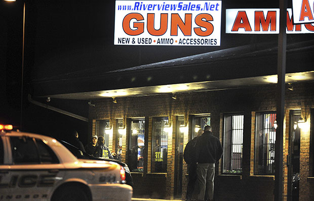Law-enforcement officials stand outside Riverview Gun Sales, December 20, 2012, as authorities raid the store in East Windsor, Connecticut.