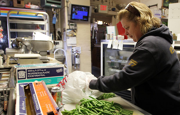 Owner of Robie's Country Deli and Store Debbie Chouinard works on cutting up green beans, December 6, 2012.