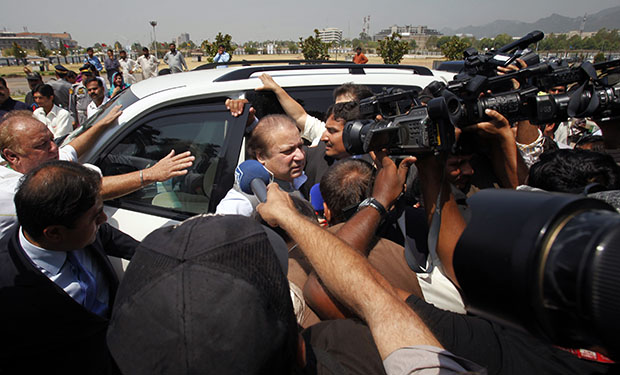 Pakistan's incoming prime minister, Nawaz Sharif, center, gets surrounded by media as he arrives to attend the first National Assembly session in Islamabad, Pakistan, Saturday, June 1, 2013.