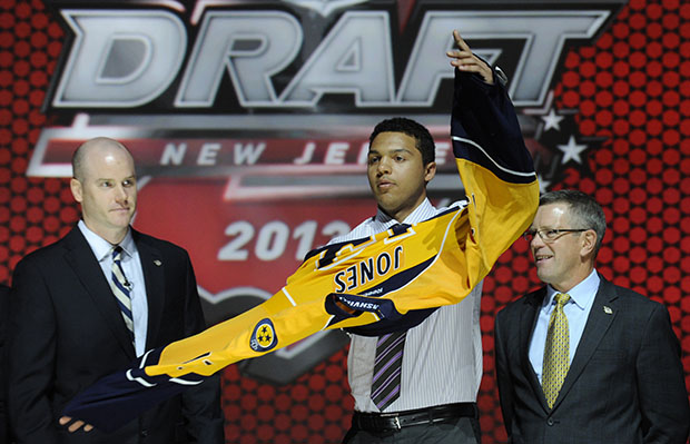 Seth Jones, a defenseman, pulls on a Nashville Predators jersey after being chosen fourth overall in the first round of the NHL hockey draft, Sunday, June 30, 2013, in Newark, New Jersey.