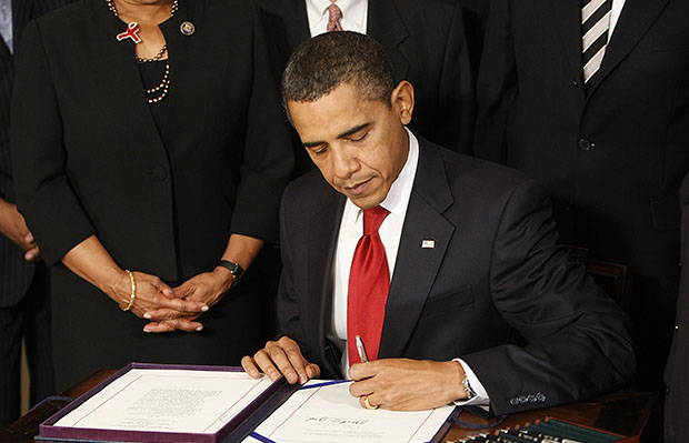 President Barack Obama signs the Ryan White HIV/AIDS Treatment Extension Act of 2009, Friday, October 30, 2009, in the Diplomatic Reception Room of the White House in Washington.