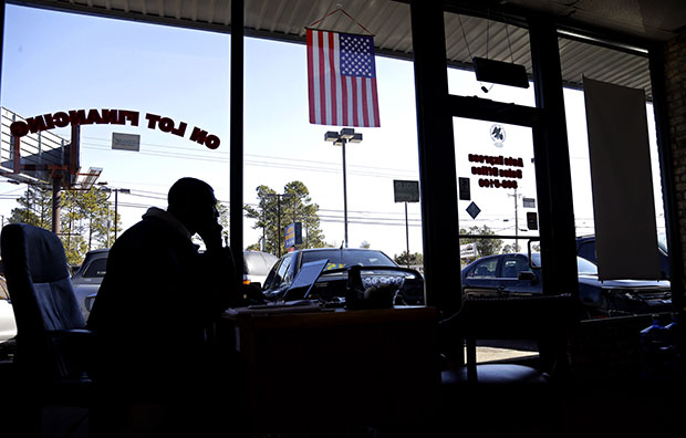 Salesman Donnie Alford talks on the phone in his office at Auto Express in Fayetteville, North Carolina, March 4, 2013. The auto and wheels business is located on Yadkin Road, near a main entrance to Fort Bragg military base.