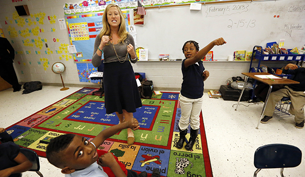 In this February 15, 2013, photo, Myrtle Hall IV Elementary School teacher Gabrielle Wooden, left, and Camilyn Anderson, 7, lead their first-grade class in a live-action Spanish class in Clarksdale, Mississippi.