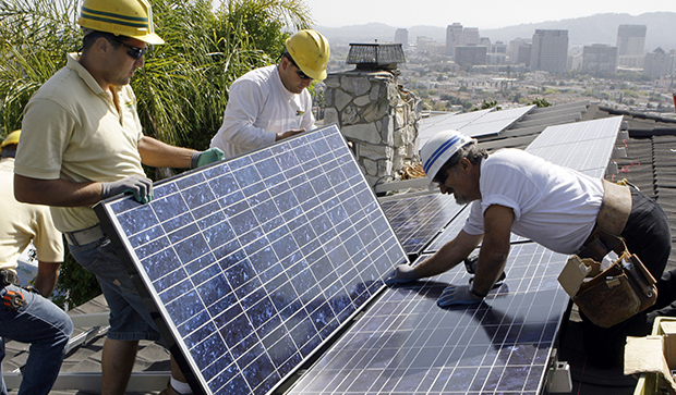 Installers Arin Gharibian, left, Hayk Mkrtchayan, and team leader Edward Boghosian, right, all employees of California Green Design, assemble solar electrical panels on the roof of a home in Glendale, California.