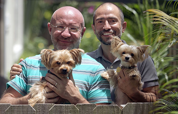 Julian Marsh, left, poses with his husband Tray Popov and their Yorkshire Terriers, Rosie, left, and Phoebe at their home, Monday, July 1, 2013, in Fort Lauderdale, Florida. Popov, who is a Bulgarian graduate student, and Marsh, a U.S. citizen, are the first gay couple in the nation to have their application for immigration benefits approved after the Supreme Court ruling on same-sex marriages, their lawyer says.