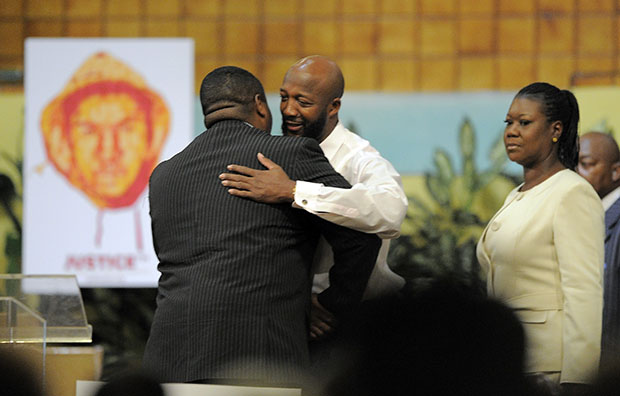 Pastor Charles Blake lll, left, greets Tracy Martin, center, and Sybrina Fulton, the parents of shooting victim Trayvon Martin, during a rally on behalf of Trayvon's family, Thursday, April 26, 2012, in Los Angeles, California.