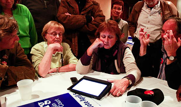 Sue Gatterman, seated second from left, Barbara Schrank, and Fred Schrank, fingers crossed, supporters for Wisconsin Supreme Court candidate JoAnne Kloppenburg, all watch election results in the supreme court race between Kloppenburg and incumbent David Prosser in Madison, Wednesday, April 6, 2011.