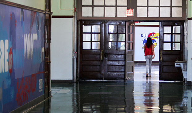 A lone student walks down a hallway at the Jean de Lafayette Elementary School, on the final day of school, Wednesday, June 19, 2013, in Chicago.