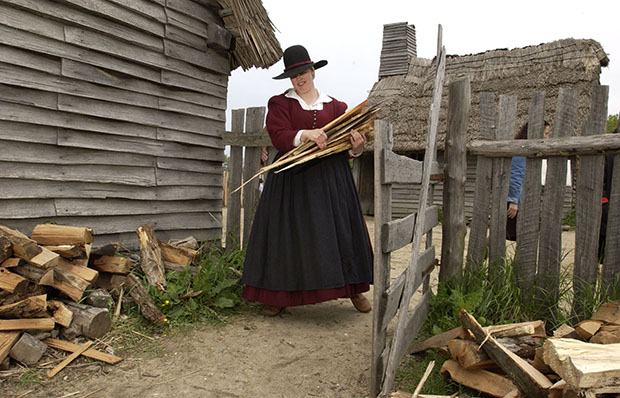 Sarah Cole carries firewood for chopping as part of her role as Plymouth colonist Alice Bradford at Plimoth Plantation in Plymouth, Massachusetts, Thursday, May 27, 2004.