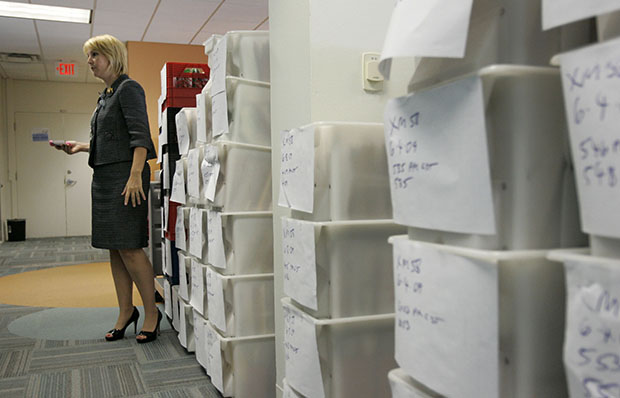 Kristi Barrows, deputy director of the U.S. Citizenship and Immigration Services Texas Service Center, stands by crates of files that are waiting to be processed by adjudicators in Dallas, June 16, 2009.