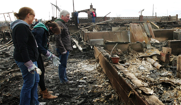 A family assesses the damage caused by a fire during Superstorm Sandy on Wednesday, October 31, 2012, in New York.