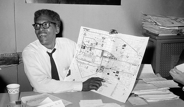 In this August 24, 1963, file photo, Bayard Rustin points to a map showing the path of the March on Washington during a news conference at the New York City headquarters.