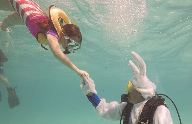 Spencer Slate, right, costumed as a scuba-diving Easter bunny, hands a hard-boiled egg to Quinn Vanischak, Sunday, March 31, 2013, during an Underwater Easter Egg Hunt in the Florida Keys National Marine Sanctuary off Key Largo, Florida.
