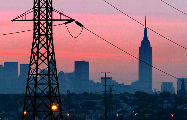 A darkened New York City is visible just before dawn through power lines from Jersey City, New Jersey, August 15, 2003. The Empire State Building is in the background.