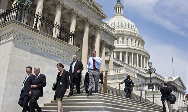 Members of Congress walk down the steps of the House of Representatives on Capitol Hill in Washington.