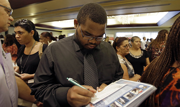 Job seeker Kelsey Devoe of Miramar, Florida, fills out a contact form at a job fair in Miami Lakes, Florida, Wednesday, August, 14, 2013.