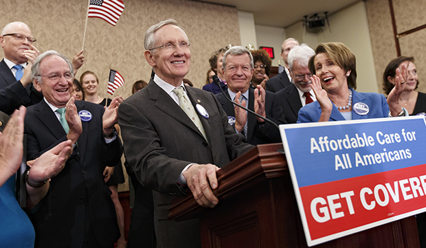 Senate Majority Leader Harry Reid (D-NV), center, accompanied by other lawmakers and people whose lives have been impacted by lack of health insurance, smiles during a news conference on Capitol Hill in Washington, Tuesday, October 1, 2013.