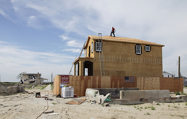 A worker walks the roof line of a house under construction in the Breezy Point community of New York's Queens borough on Wednesday, July 24, 2013. It is the first house to be rebuilt in the beachfront community, where more than 110 homes burned to the ground during Superstorm Sandy in October 2012.